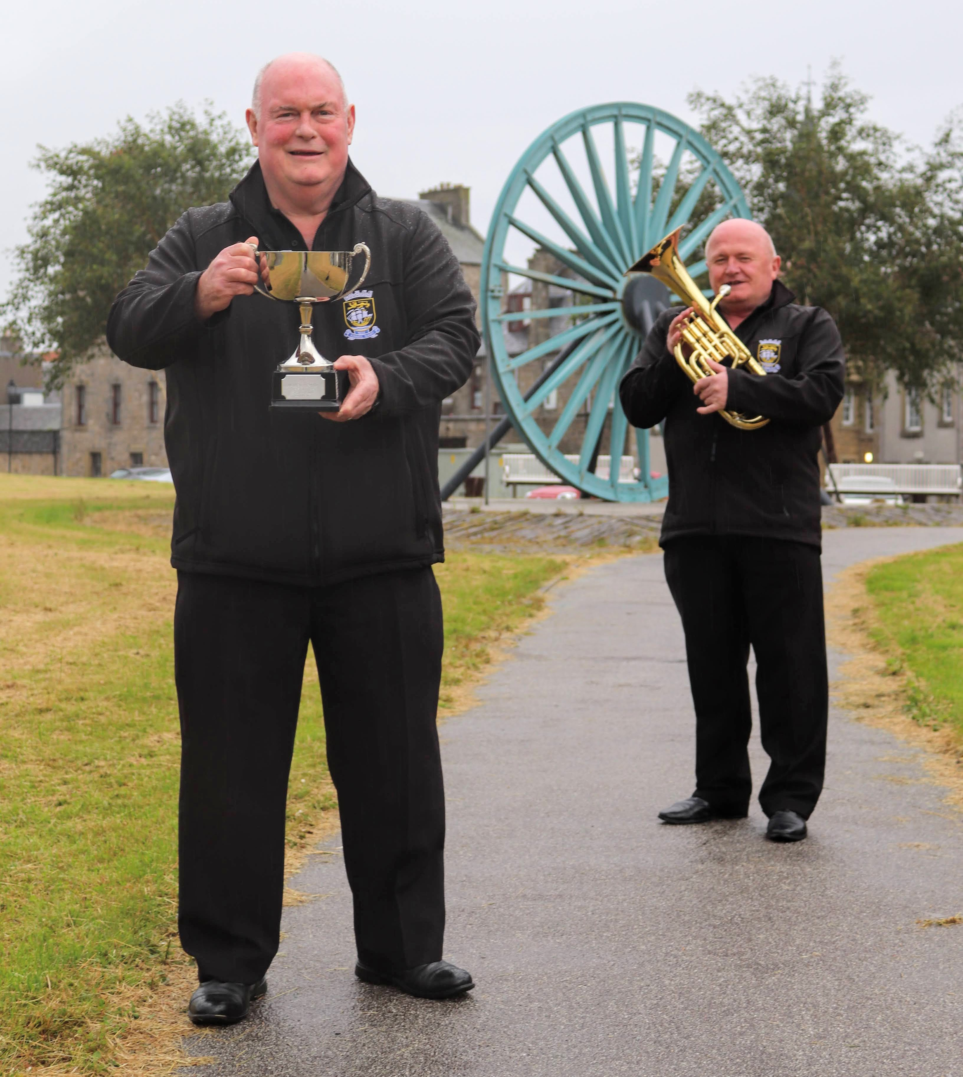 Brian Holmes and Robert Doherty from UNISON Kinneil Band celebrate the band's success winning the 2020 McLaren Trophy from Bo'ness Community Council.